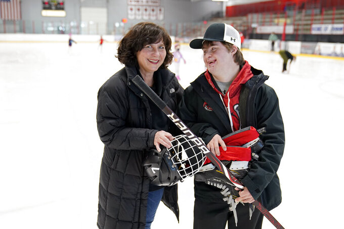 Suzy Lindeberg poses with her 20-year-old son John on a hockey rink, Tuesday, Feb. 9, 2021 in Stillwater, Minn. John, who has Down Syndrome, can't spend as much time at the rink as he used to since he is at a higher risk for hospitalization or death if he caught COVID-19, but his mother and other advocates worry that the state of Minnesota has placed people with disabilities too far down the priority list.  (AP Photo/Jim Mone)