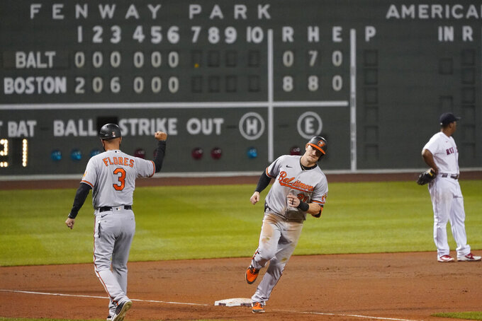 Baltimore Orioles' Austin Hays, center, rounds the bases after hitting a solo home run off Boston Red Sox relief pitcher Mike Kickham during the seventh inning of a baseball game in Boston, Wednesday, Sept. 23, 2020, at Fenway Park. At left is Orioles third base coach Jose Flores. (AP Photo/Charles Krupa)