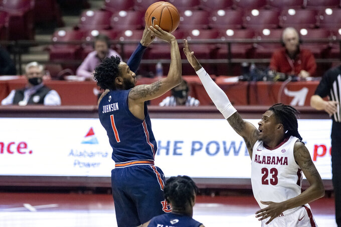 Auburn guard Jamal Johnson (1) shoots a jumper over Alabama guard John Petty Jr. (23) during the first half of an NCAA college basketball game Tuesday, March 2, 2021, in Tuscaloosa, Ala. (AP Photo/Vasha Hunt)