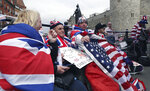 Royal fans John Loughry, right, and Terry Hutt, center, show off their placards as TV and journalists film and interview them in just outside Windsor Castle, in Windsor, England, Wednesday, May 16, 2018. Preparations continue in Windsor ahead of the royal wedding of Britain's Prince Harry and Meghan Markle Saturday May 19, which includes a 30 minute carriage route taking the couple round the town to wave to the crowds, some of whom are already taking up positions . (AP Photo/Alastair Grant)