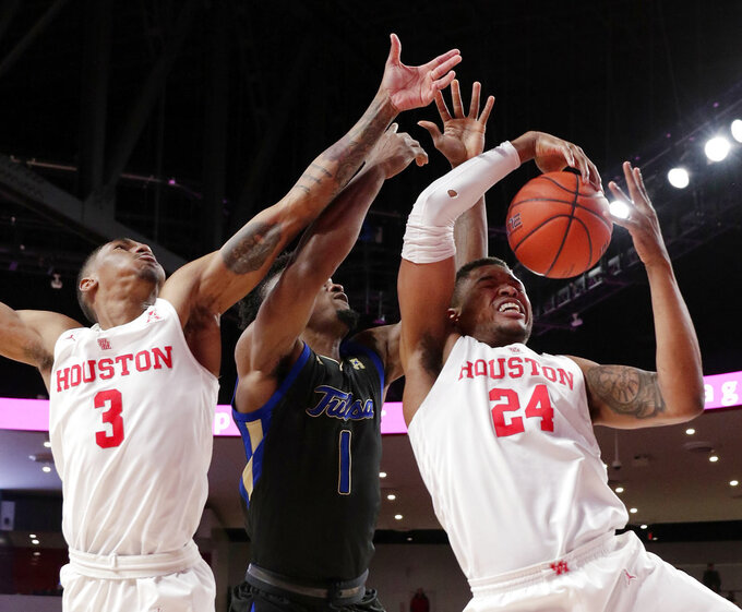 Houston forward Breaon Brady (24) gets the rebound from Tulsa forward Martins Igbanu (1) as guard Armoni Brooks (3) reaches during the first half of an NCAA college basketball game Wednesday, Jan. 2, 2019, in Houston. (AP Photo/Michael Wyke)