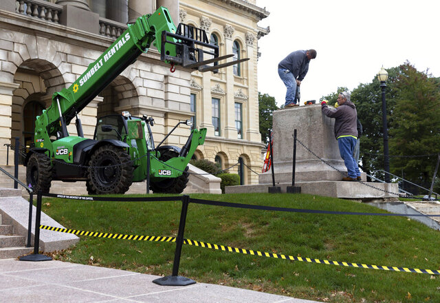 Crews work to mount a plate on top of the pedestal where a statue of Stephen A. Douglas, a 19th century senator from Illinois who owned slaves and was a longtime nemesis of Abraham Lincoln, stood outside the Illinois State Capitol, Monday, Sept. 28, 2020, in Springfield, Ill. The statue was removed on Saturday. (Justin L. Fowler/The State Journal-Register via AP)