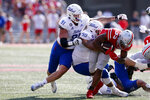 Ohio State running back Master Teague, right, is tackled by Tulsa defensive lineman Cullen Wick, left, and defensive lineman Jaxon Player during the first half of an NCAA college football game Saturday, Sept. 18, 2021, in Columbus, Ohio. (AP Photo/Jay LaPrete)