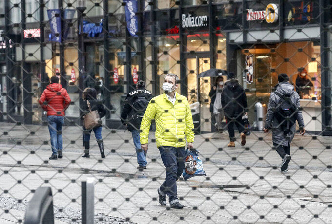 FILE - In this Feb. 2, 2021 file photo, a few people walking at the main shopping street are seen through a closed gate of an abandoned shopping center during the lockdown in Essen, Germany. The European Union statistics agency Eurostat announces first-quarter growth figures for the 19 countries that use the euro. (AP Photo/Martin Meissner, File)
