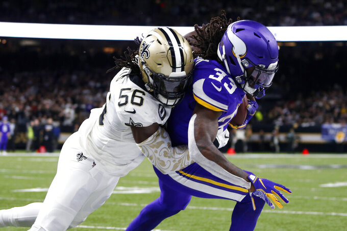 Minnesota Vikings running back Dalvin Cook (33) is stopped near the goal line by New Orleans Saints outside linebacker Demario Davis (56) in the first half of an NFL wild-card playoff football game, Sunday, Jan. 5, 2020, in New Orleans. (AP Photo/Butch Dill)