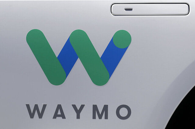 FILE - In this May 8, 2018, file photo, a Waymo logo is displayed on the door of a car at the Google I/O conference in Mountain View, Calif.  Waymo is allowing the general public to hitch a ride in its driverless autonomous vehicles in Phoenix, Thursday, Oct. 8, 2020. It's expanding a service it had been quietly offering to a select group of riders for the past year.  (AP Photo/Jeff Chiu, File)