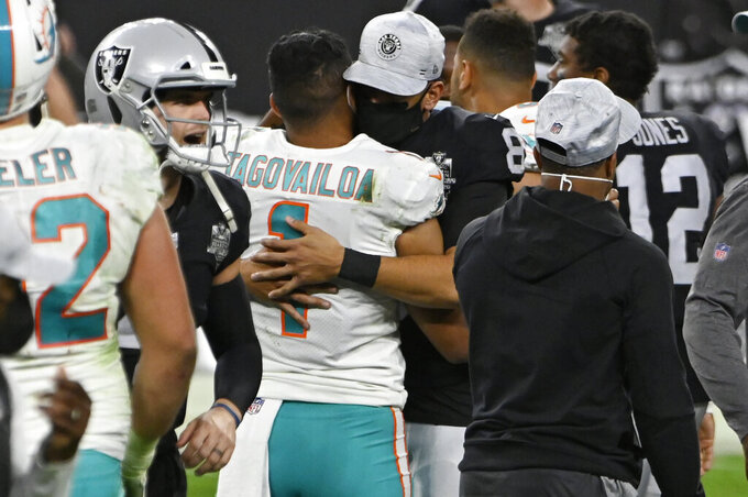 Miami Dolphins quarterback Tua Tagovailoa (1) embraces Las Vegas Raiders quarterback Marcus Mariota (8) after an NFL football game, Saturday, Dec. 26, 2020, in Las Vegas. (AP Photo/David Becker)