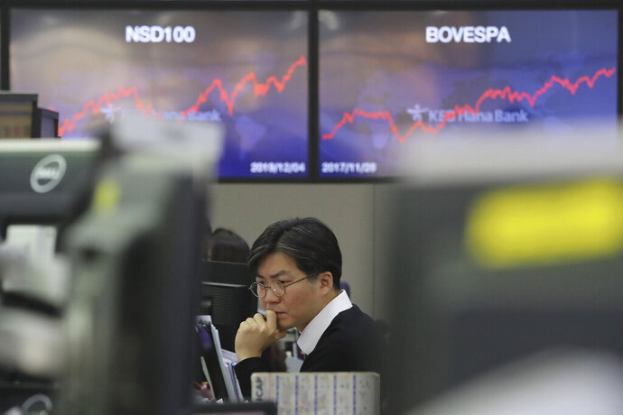 A currency trader watches monitors at the foreign exchange dealing room of the KEB Hana Bank headquarters in Seoul, South Korea, Thursday, Dec. 5, 2019. Asian shares were rising Thursday amid renewed hopes a U.S. trade deal with China may be nearing, despite tough recent talk from President Donald Trump.(AP Photo/Ahn Young-joon)