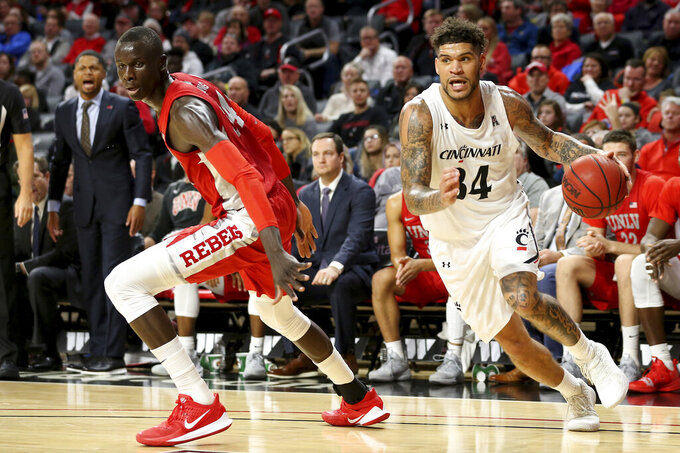 Cincinnati guard Jarron Cumberland (34) drives to the basket as UNLV forward Cheikh Mbacke Diong (34) defends during the first half of an NCAA college basketball game Saturday, Nov. 30, 2019, in Cincinnati. (Kareem Elgazzar/The Cincinnati Enquirer via AP)