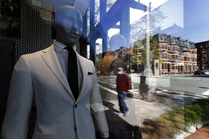 FILE - This April 29, 2020 file photo, a passer-by wearing a mask out of concern for the COVID-19 coronavirus, background center, walks past mannequins in a clothing store in Boston.  The nation's small businesses slashed more than 11 million jobs in April as they were forced to close or suffered steep revenue losses amid the coronavirus outbreak. That report comes from payroll provider ADP, which counted the jobs lost at its business customers with under 500 workers. (AP Photo/Steven Senne, File)