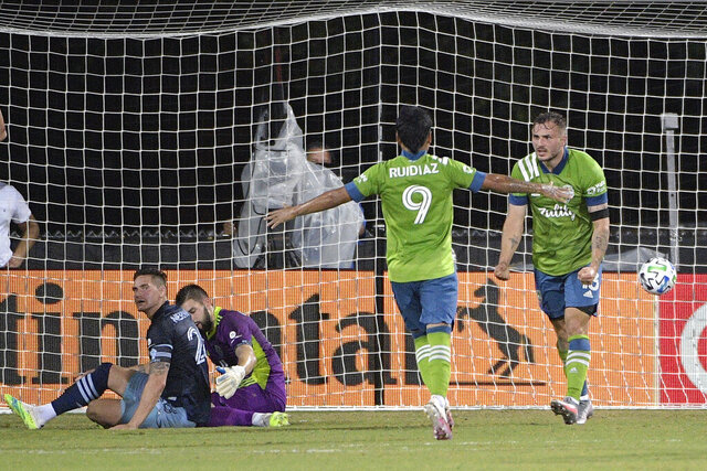 Seattle Sounders forward Jordan Morris, right, celebrates after scoring a goal past Vancouver Whitecaps defender Jake Nerwinski, left, and goalkeeper Maxime Crepeau during the first half of an MLS soccer match, Sunday, July 19, 2020, in Kissimmee, Fla. Coming to congratulate Morris is Sounders forward Raul Ruidiaz (9). (AP Photo/Phelan M. Ebenhack)