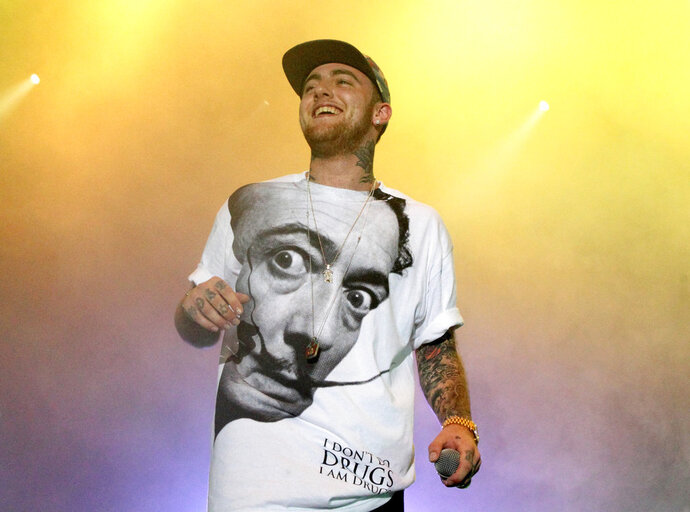 FILE - In this July 13, 2013, file photo, Rapper Mac Miller performs on his Space Migration Tour at Festival Pier in Philadelphia. Ariana Grande has posted a tribute to her ex-boyfriend Mac Miller a week after his death, saying she's sorry she couldn't save him. Paramedics declared the 26-year-old Miller dead in his Los Angeles home Sept. 7. (Photo by Owen Sweeney/Invision/AP, File)