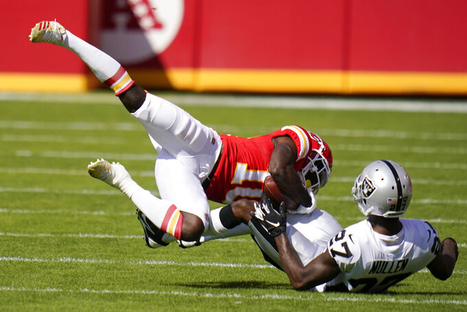 Kansas City Chiefs wide receiver Tyreek Hill (10) catches a pass over Las Vegas Raiders cornerback Trayvon Mullen (27) during the first half of an NFL football game, Sunday, Oct. 11, 2020, in Kansas City. (AP Photo/Jeff Roberson)