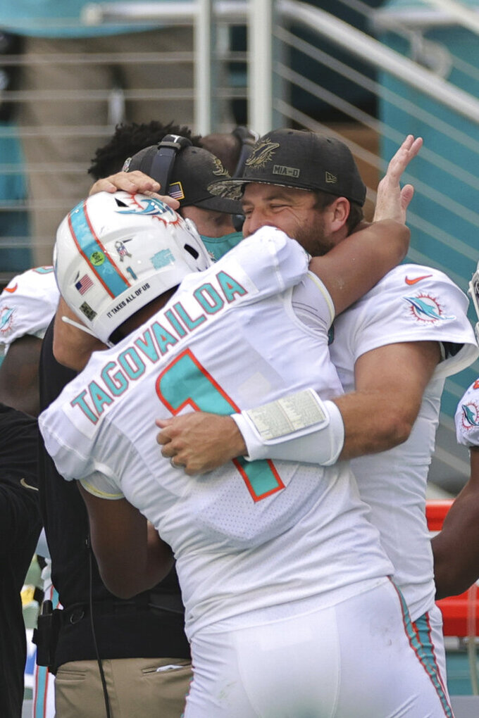 Miami Dolphins quarterback Tua Tagovailoa (1) and quarterback Ryan Fitzpatrick (14) embrace after Tagovailoa throws his first touchdown pass during an NFL game against the Los Angeles Rams, Sunday, Nov. 1, 2020 in Miami Gardens, Fla. The Dolphins defeated the Rams 28-17. (Margaret Bowles via AP)