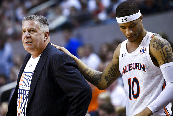 Auburn guard Samir Doughty (10) stands with coach Bruce Pearl after a foul call during the first half of the team's NCAA college basketball game against Kentucky on Saturday, Feb. 1, 2020, in Auburn, Ala. (AP Photo/Julie Bennett)