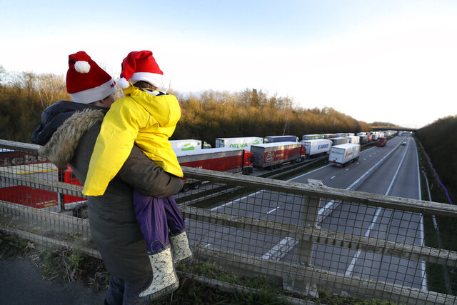 A mother and child look at the line of trucks parked up on the M20, part of Operation Stack in Ashford, Kent, England, Friday, Dec. 25, 2020. Thousands wait to resume their journey across The Channel after the borders with France reopened. Trucks inched slowly past checkpoints in Dover and headed across the Channel to Calais on Thursday after France partially reopened its borders following a scare over a rapidly spreading new virus variant. (AP Photo/Kirsty Wigglesworth)
