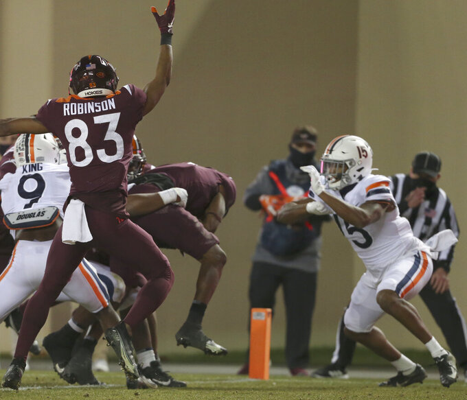 Virginia Tech's Tré Turner, second from right, scores a touchdown against Virginia during the first half of an NCAA college football game Saturday, Dec. 12, 2020, in Blacksburg, Va. (Matt Gentry/The Roanoke Times via AP, Pool)