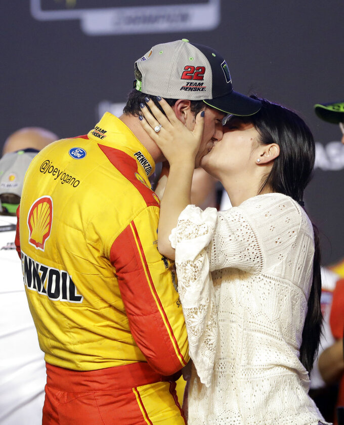 Joey Logano kisses his wife Brittany Baca after winning the NASCAR Cup Series Championship auto race at the Homestead-Miami Speedway, Sunday, Nov. 18, 2018, in Homestead, Fla. (AP Photo/Lynne Sladky)