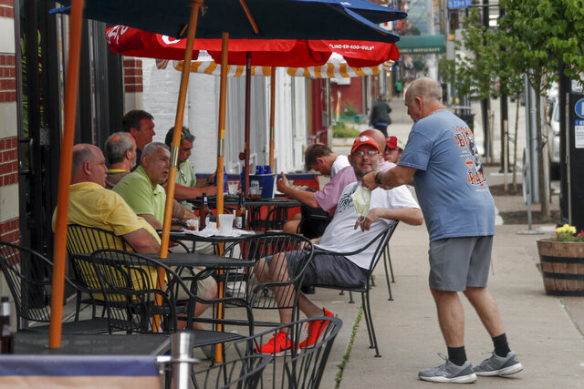 People take advantage of newly lowered COVID-19 protective restrictions in most of southwest Pennsylvania and have food and drinks on the sidewalk on the re-opening day for seated patrons at an eatery on Pittsburgh's Southside, Friday, June 5, 2020. (AP Photo/Keith Srakocic)