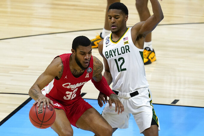 Houston forward Reggie Chaney (32) drives on Baylor guard Jared Butler (12) during the first half of a men's Final Four NCAA college basketball tournament semifinal game, Saturday, April 3, 2021, at Lucas Oil Stadium in Indianapolis. (AP Photo/Darron Cummings)