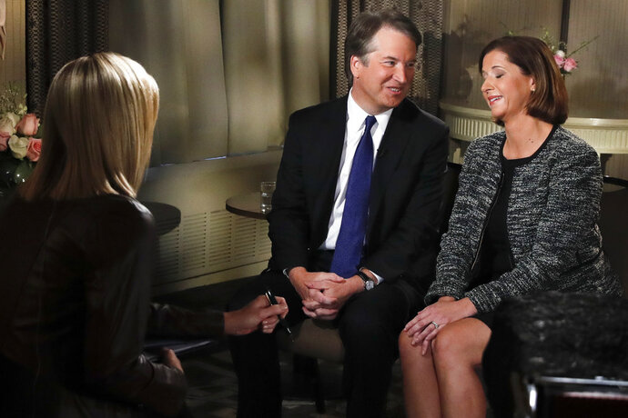 Brett Kavanaugh looks at his wife Ashley Estes Kavanaugh at the start of a FOX News interview with Martha MacCallum, Monday, Sept. 24, 2018, in Washington, about allegations of sexual misconduct against the Supreme Court nominee. (AP Photo/Jacquelyn Martin)