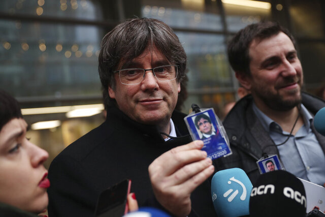Catalonia's former regional president Carles Puigdemont, center, shows his accreditation badge as he stands next to former Catalan regional minister Antoni Comin outside the European Parliament in Brussels, Friday, Dec. 20, 2019. In a potentially stinging reversal for Spanish justice authorities, the European Union's top court ruled that a former Catalan official serving a prison sentence for his role in a banned independence referendum two years ago had the right to parliamentary immunity when he was on trial. (AP Photo/Francisco Seco)