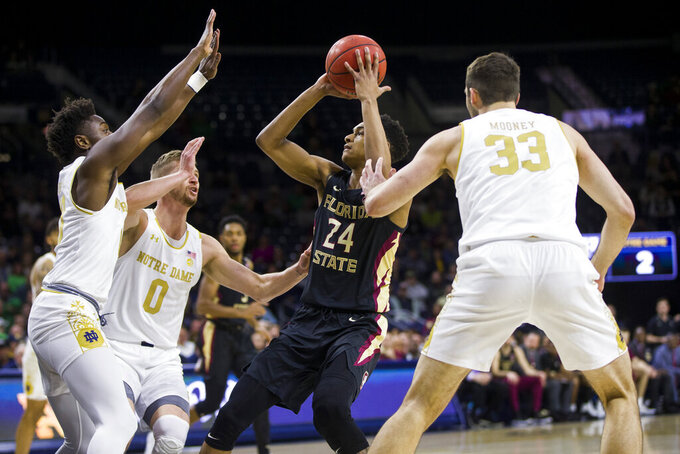 Florida State's Devin Vassell (24) looks for a shot as Notre Dame's Prentiss Hubb, left, Rex Pflueger (0) and John Mooney (33) defend during the first half of an NCAA college basketball game Wednesday, March 4, 2020, in South Bend, Ind. (AP Photo/Robert Franklin)