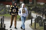 Matthew Hammerschmidt, right, and Dasan Zahn, both of Bismarck, N.D., visit Old Granary Burying Ground in Boston, Saturday, March, 14, 2020. Fans of the Boston Bruins, they had flown in specifically for Saturday night's game against the Toronto Maple Leafs. The pair said they learned that the NHL had suspended play due to concern about the coronavirus just as the plane was touching down in Boston. For most people, the new coronavirus causes only mild or moderate symptoms, such as fever and cough. For some, especially older adults and people with existing health problems, it can cause more severe illness, including pneumonia. The vast majority of people recover from the new virus. (AP Photo/Michael Dwyer)