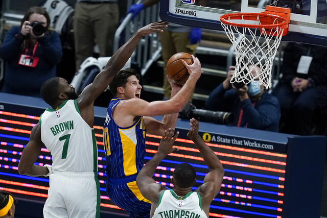 Indiana Pacers' Doug McDermott (20) puts up a shot against Boston Celtics' Jaylen Brown (7) during the first half of an NBA basketball game, Sunday, Dec. 27, 2020, in Indianapolis. (AP Photo/Darron Cummings)