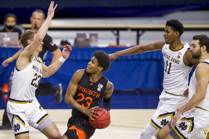 Miami's Kameron McGusty, center, drives between Notre Dame's Dane Goodwin, left, Juwan Durham (11) and Nikola Djogo during the second half of an NCAA college basketball game Sunday, Feb. 14, 2021, in South Bend, Ind. Notre Dame won 71-61. (AP Photo/Robert Franklin)