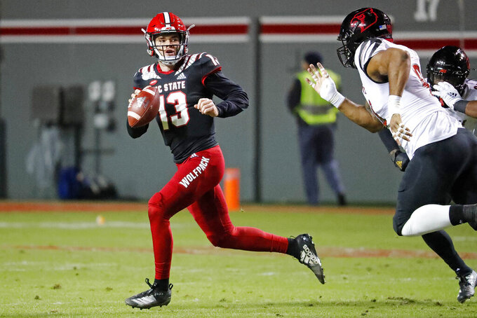 North Carolina State's Devin Leary (13) scrambles away from Louisville's Jared Goldwire (90) during the first half of an NCAA college football game in Raleigh, N.C., Saturday, Nov. 16, 2019. (AP Photo/Karl B DeBlaker)
