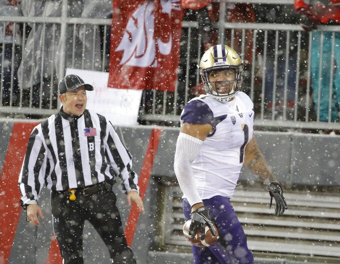 In this Nov. 23, 2018 photo, Washington tight end Hunter Bryant holds the football after he made a catch for a touchdown against Washington State during the Apple Cup NCAA college football game in Pullman, Wash. After spending more than half the season recovering from knee surgery in June 2018, Bryant has provided a boost for the Washington offense heading into the Pac-12 championship game against Utah on Friday, Nov. 30, 2018. (AP Photo/Ted S. Warren)