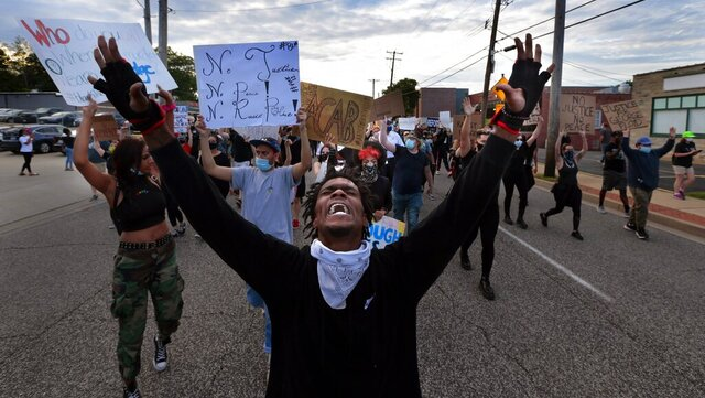 Protesters march on South Florissant Road in front of the Ferguson police station on Saturday, May 30, 2020, demonstrating against the death of George Floyd in custody of Minneapolis police officers. (Robert Cohen/St. Louis Post-Dispatch via AP)