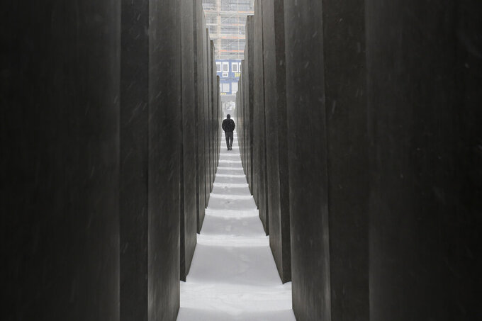 FILE - In this Feb.7, 2021 file photo a man visits the Holocaust Memorial during snowfall in central Berlin, Germany. Germany has committed millions of dollars in extra funding to survivors of the Nazi Holocaust to help ensure that all of them are able to get vaccinated against the coronavirus, the organization that handles claims on behalf of Jewish victims said Wednesday.(AP Photo/Markus Schreiber)