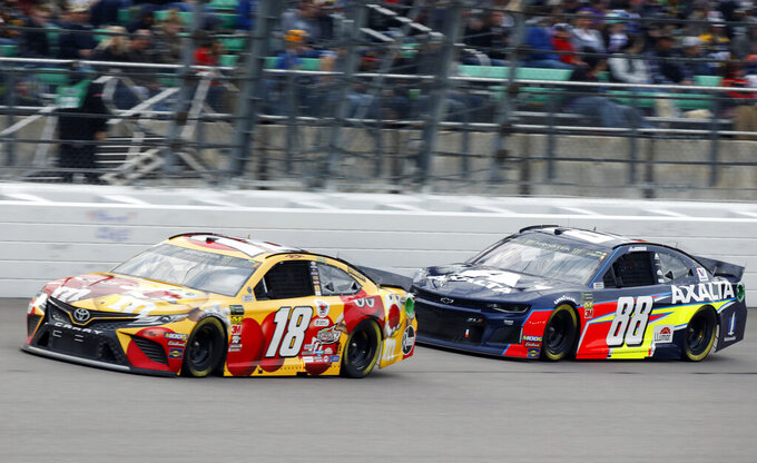 Kyle Busch (18) drives in front of Alex Bowman (88) during the NASCAR Cup Series auto race at Kansas Speedway in Kansas City, Kan., Saturday, May 11, 2019. (AP Photo/Colin E. Braley)