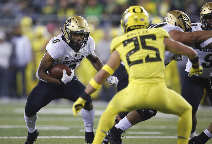 Colorado's Alex Fontenot, left, rushes as Oregon's Brady Breeze defends during the second quarter of an NCAA college football game Friday, Oct. 11, 2019, in Eugene, Ore. (AP Photo/Chris Pietsch)