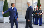 French President Emmanuel Macron, left, welcomes Tunisian President Kais Saied for bilateral talks at the Elysee Palace in Paris, Monday, June 22, 2020. Tunisian President Kais Saied is for a two-day visit in France. (AP Photo/Michel Euler)