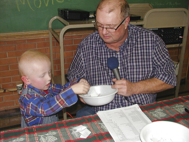 In a photo provided by Carolyn Plotts, Eric Kuhlman, 3, helps master of ceremonies Stan Miller draw names for the annual Norcator drawing held in Norcatur, Kan. For the 150 or so people who still call the rural hamlet home, the cancellation this year of the town's beloved Norcatur Christmas Drawing has shone a spotlight on a global coronavirus pandemic that has reached deep into rural America. (Carolyn Plotts via AP)