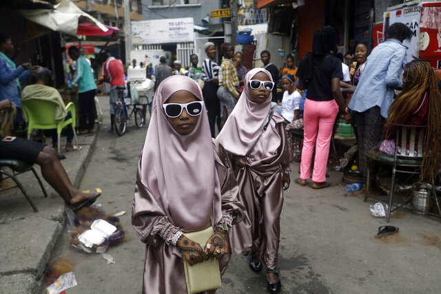 Muslim girls walk through a street after prayers in Lagos, Nigeria, Friday, July 31, 2020. (AP Photo/Sunday Alamba, File)
