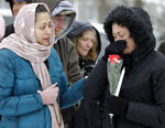 People cry at a makeshift memorial Sunday, Feb. 17, 2019, in Aurora, Ill., near Henry Pratt Co. manufacturing company where several were killed on Friday. Authorities say an initial background check five years ago failed to flag an out-of-state felony conviction that would have prevented a man from buying the gun he used in the mass shooting in Aurora. (AP Photo/Nam Y. Huh)