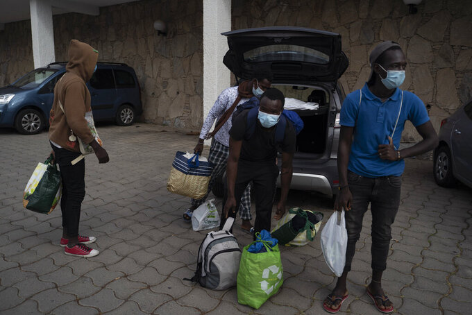 Migrants from Senegal, including alleged minors, who were sleeping in the streets of Las Palmas arrive with their belongings to Holiday Club Puerto Calma hotel in Puerto Rico de Gran Canaria, Spain, March 31, 2021. With hundreds of empty rooms, hotel director Calvin Lucock and restaurant owner Unn Tove Saetran decided to reopen their doors at their own expense to provide food, shelter and care to young migrant men who fell out of the official reception and integration system. (AP Photo/Renata Brito)