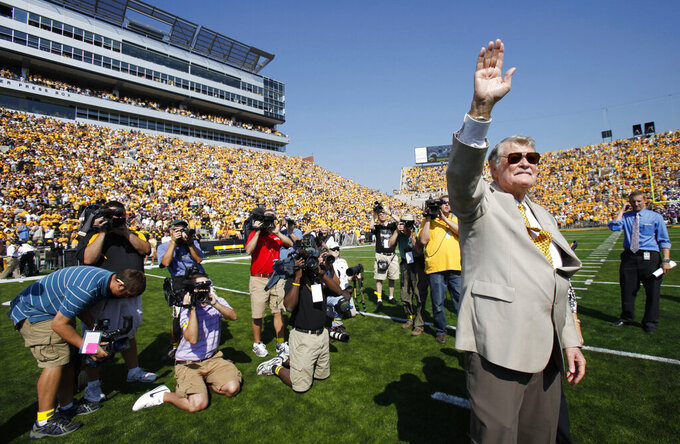 FILE - In this Saturday, Sept. 5, 2009, file photo, former Iowa football coach Hayden Fry waves to the crowd as he is introduced before Iowa's NCAA college football game against Northern Iowa, in Iowa City, Iowa. Fry, the Texan who revived Iowa football and became a Hawkeye State institution, died Tuesday, Dec. 17, 2019, after a long battle with cancer. He was 90. (AP Photo/Charlie Neibergall, File)
