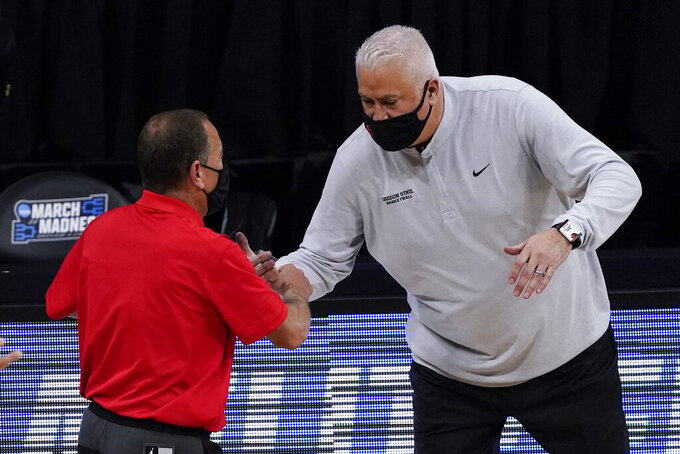 Houston head coach Kelvin Sampson and Oregon State head coach Wayne Tinkle shake hands after an Elite 8 game in the NCAA men's college basketball tournament at Lucas Oil Stadium, Monday, March 29, 2021, in Indianapolis. Houston won 67-61. (AP Photo/Darron Cummings)