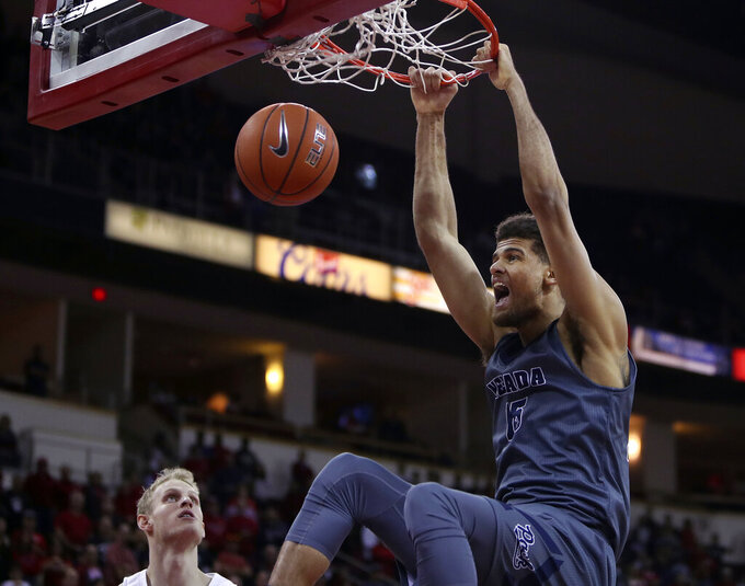 Nevada's Trey Porter, right, dunks over Fresno State's Sam Bittner during the first half of an NCAA college basketball game in Fresno, Calif., Saturday, Jan. 12, 2019. (AP Photo/Gary Kazanjian)