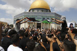 Protesters wave a Palestinian flag and one in the crowd holds a spoon, which has become a symbol celebrating the six Palestinian prisoners who tunneled out of Gilboa Prison, after Friday prayers at the Dome of the Rock Mosque in the Al Aqsa Mosque compound in in the Old City of Jerusalem, Friday, Sept. 10, 2021. (AP Photo/Mahmoud Illean)