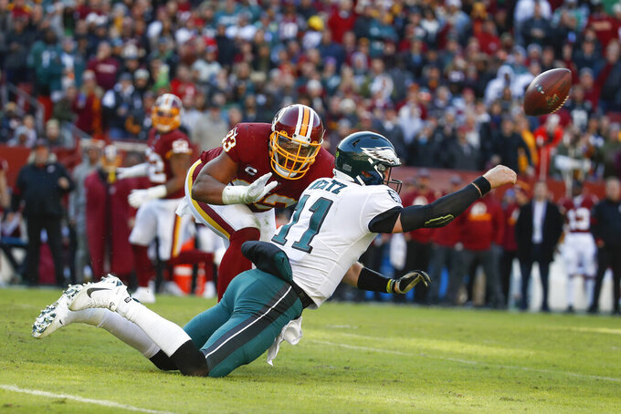 Philadelphia Eagles quarterback Carson Wentz (11) passes the ball as he trips while being chased by Washington Redskins defensive end Jonathan Allen (93) in the first half of an NFL football game, Sunday, Dec. 15, 2019, in Landover, Md. (AP Photo/Alex Brandon)