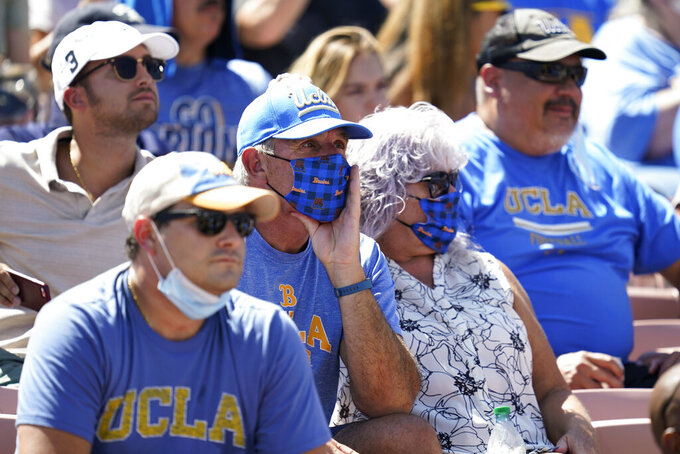 Fans, some wearing masks, sit in the stands during an NCAA college football game between Hawaii and UCLA on Saturday, Aug. 28, 2021, in Pasadena, Calif. (AP Photo/Ashley Landis)
