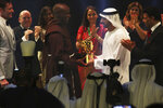 Kenyan teacher Peter Tabichi, center left, receives a statue from Dubai crown prince Sheikh Hamdan bin Mohammed Al Maktoum, center right, after winning the $1 million Global Teacher Prize in Dubai, United Arab Emirates, Sunday, March 24, 2019. Tabichi is a science teacher who gives away 80 percent of his income to the poor in the remote Kenyan village of Pwani. (AP Photo/Jon Gambrell)
