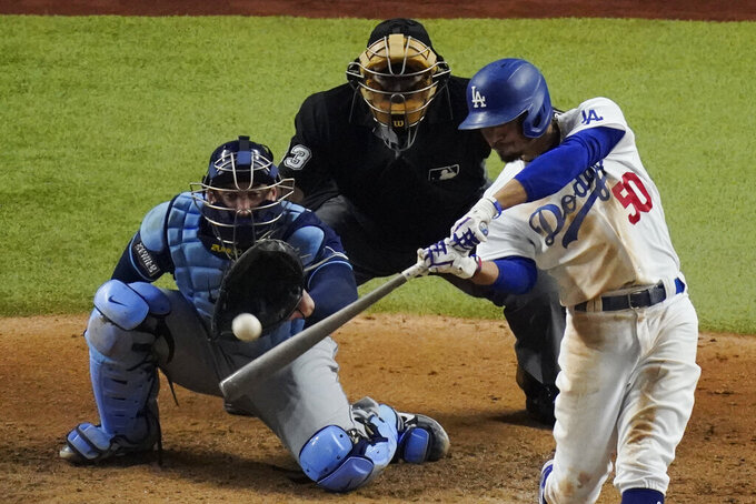 Los Angeles Dodgers' Mookie Betts hits a home run against the Tampa Bay Rays during the sixth inning in Game 1 of the baseball World Series Tuesday, Oct. 20, 2020, in Arlington, Texas. (AP Photo/Sue Ogrocki)