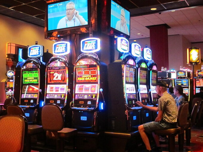This June 23, 2021 photo shows gamblers playing slot machines at Bally's casino in Atlantic City N.J. New Jersey's casinos and the three horse tracks that offer sports betting won over $450 million in July, an increase of over 70% from a year ago. (AP Photo/Wayne Parry)